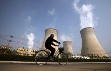 A woman rides her bicycle past the chimneys of a power station located on the outskirts of Beijing