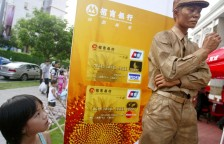 A gold-painted model promotes credit cards for a Chinese bank in Shenzhen.