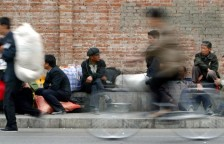 A CYCLIST RIDES PAST MIGRANT WORKERS AT A LONG DISTANCE BUS STATION IN BEIJING.