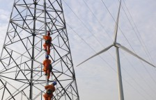 Employees climb up an electricity pylon next to a windmill to carry on a routine inspection at a wind power plant in Mingguang
