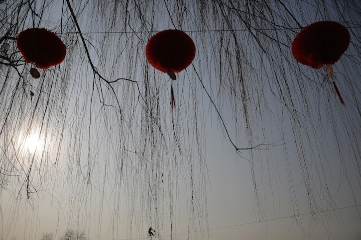 An acrobat performs on a tightrope as the Chinese Lunar New Year which welcomes the Year of the Monkey is celebrated at Daguanyuan park in Beijing