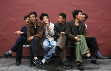 Migrant workers rest near a red wall beside the Tiananmen Square in Beijing