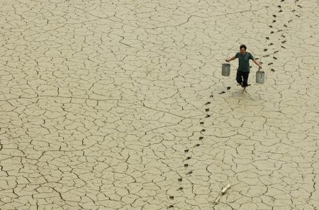 A farmer walks on a dried-up pond on the outskirts of Baokang