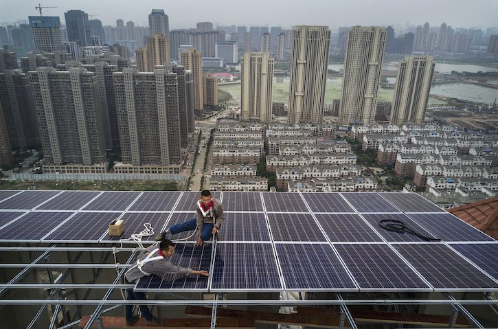 WUHAN, CHINA - MAY 14: Chinese workers from Wuhan Guangsheng Photovoltaic Company work on a solar panel project on the roof of a 47 story building in a new development on May 14, 2017 in Wuhan, China. China consumes more electricity than any other nation, but it is also the world's biggest producer of solar energy. Capacity in China hit 77 gigawatts in 2016 which helped a 50% jump in solar power growth worldwide. China is now home to two-thirds of the world's solar production, though capacity and consumption remain low relative to its population.  Still, the country now buys half of the world's new solar panels Ñ which convert sunlight into energy,  and are being installed on rooftops in cities and across sprawling fields in rural areas.  Greenpeace estimates that by 2030, renewable energy could replace fossil fuels as China's primary source of power, a significant change in a country considered the world's biggest polluter.  China's government has officially committed to development of renewable energies to ease the countryÕs dependence on coal and other fossil fuels, though its strategic investments in the solar panel have created intense global competition. (Photo by Kevin Frayer/Getty Images)